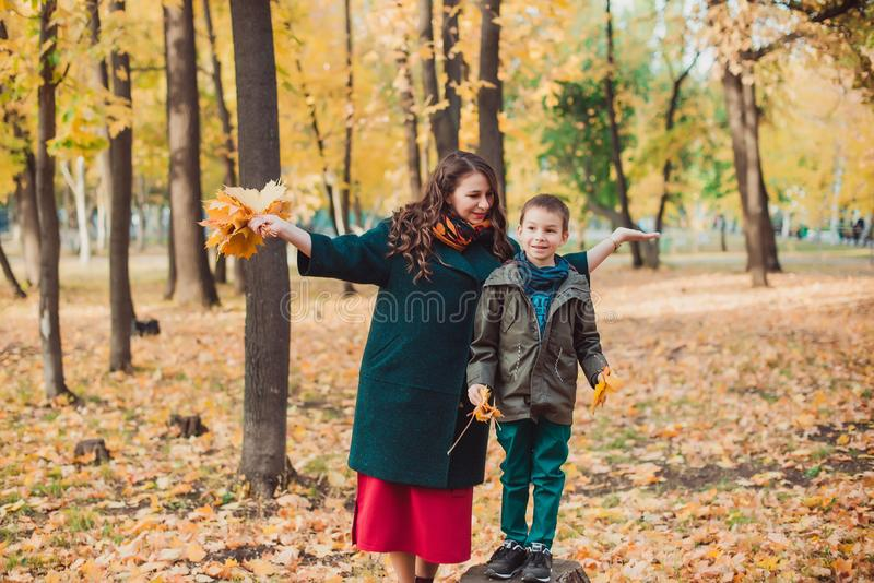 La mamá y el hijo caminan en el parque del otoño Familia feliz Concepto del otoño imagen de archivo libre de regalías