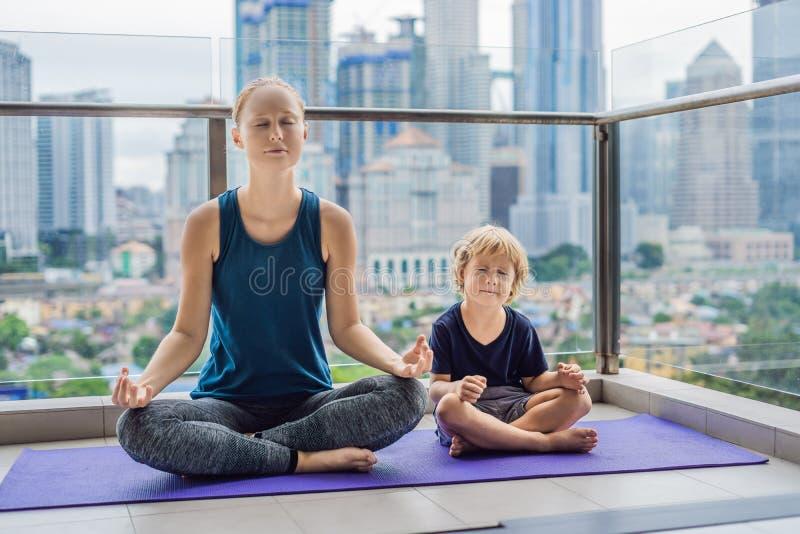 La mamá y el hijo están practicando yoga en el balcón en el fondo imagenes de archivo