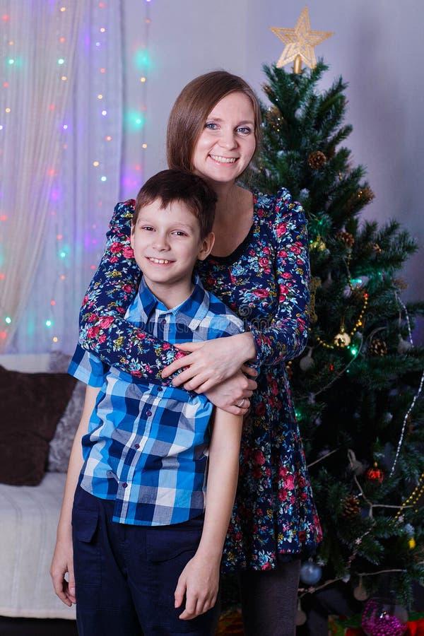 la mamá y el hijo felices en casa celebran la Navidad, el humor del Año Nuevo, el árbol de navidad y los regalos foto de archivo