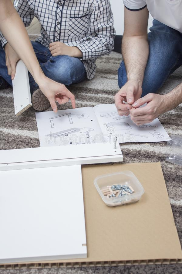 La mamá y el hijo gastan sus propios muebles Se sientan en la alfombra y comparan el mueble con el ejemplo en el asse fotografía de archivo libre de regalías