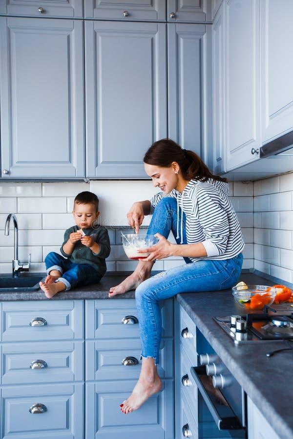 La mamá y el hijo se están sentando en la tabla en la cocina fotografía de archivo libre de regalías