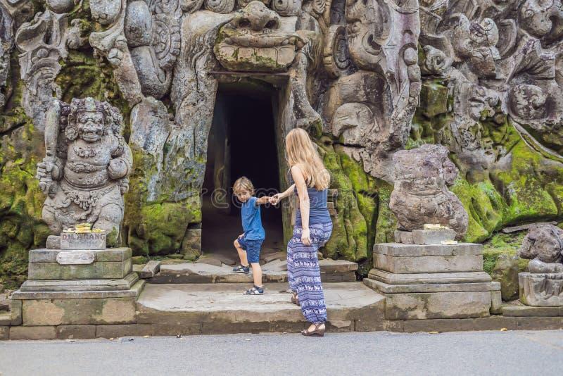 La mamá y el hijo son turistas en el templo hindú viejo de Goa Gajah cerca de U imagenes de archivo