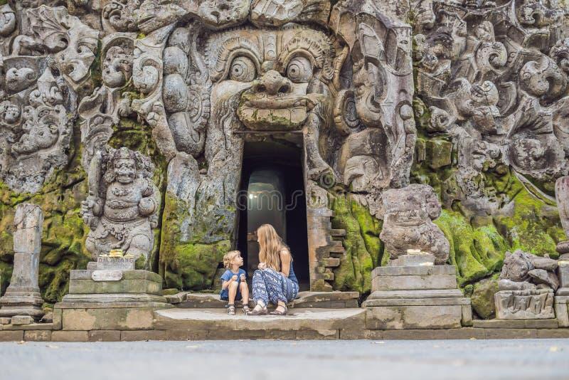 La mamá y el hijo son turistas en el templo hindú viejo de Goa Gajah cerca de U fotografía de archivo libre de regalías