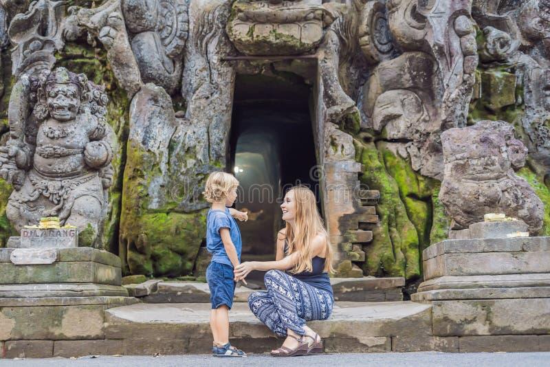 La mamá y el hijo son turistas en el templo hindú viejo de Goa Gajah cerca de U imágenes de archivo libres de regalías