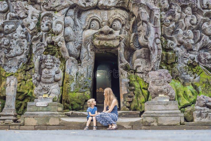La mamá y el hijo son turistas en el templo hindú viejo de Goa Gajah cerca de U fotos de archivo