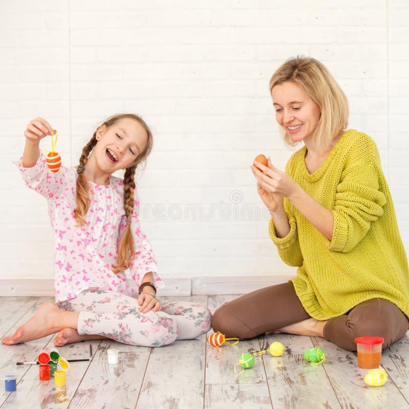 La mamá y el niño adornan los huevos de Pascua foto de archivo
