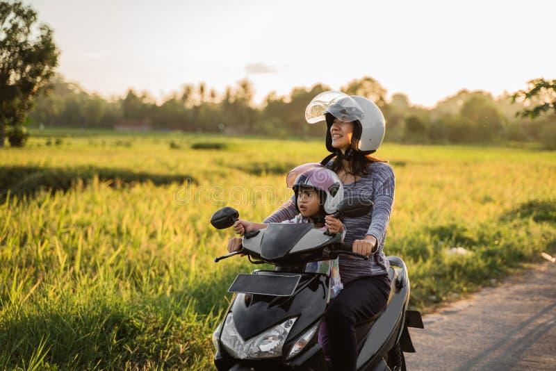 La mamá y el niño gozan el montar de la vespa de la motocicleta imágenes de archivo libres de regalías