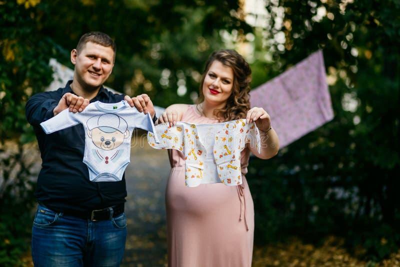 La mamá y el papá futuros preparan la ropa del bebé para su niño nonato imágenes de archivo libres de regalías