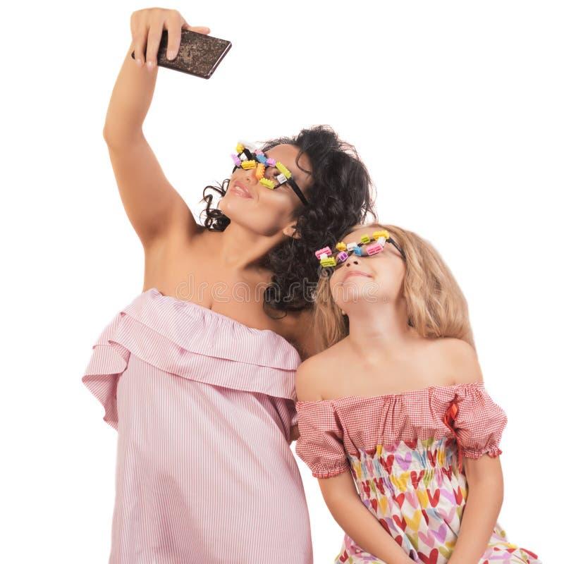 La mamá y la hija adolescente hacen el selfie Aislado en el fondo blanco Selfie sonriente en vidrios divertidos fotografía de archivo