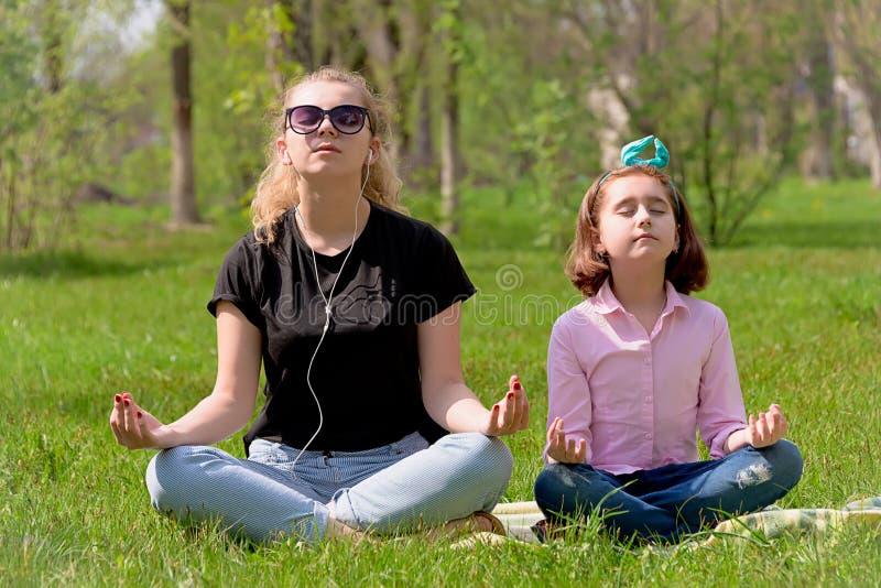 La mamá y la hija descansan sobre la hierba verde foto de archivo