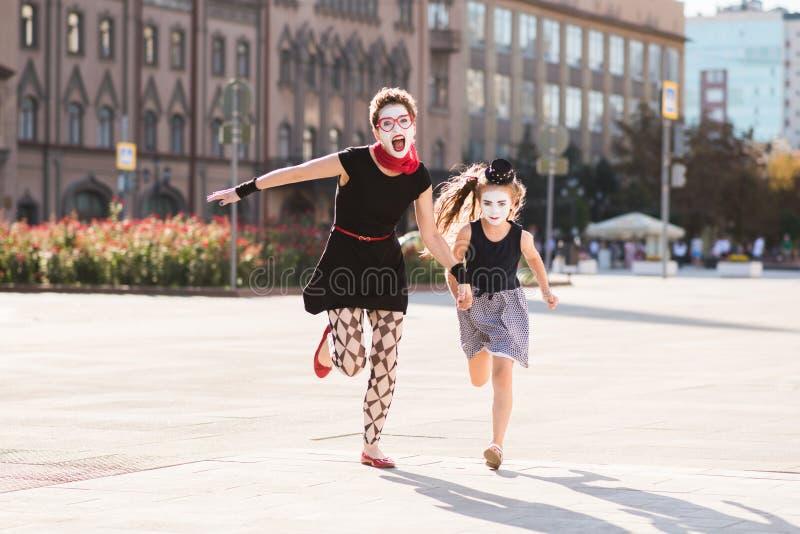 La mamá y la hija están corriendo a lo largo del camino imágenes de archivo libres de regalías