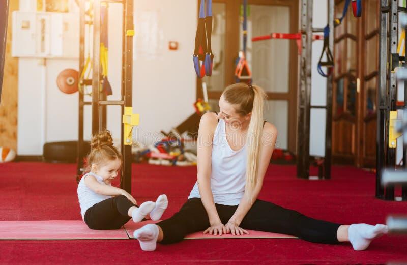 La mamá y la hija juntos realizan diversos ejercicios fotografía de archivo