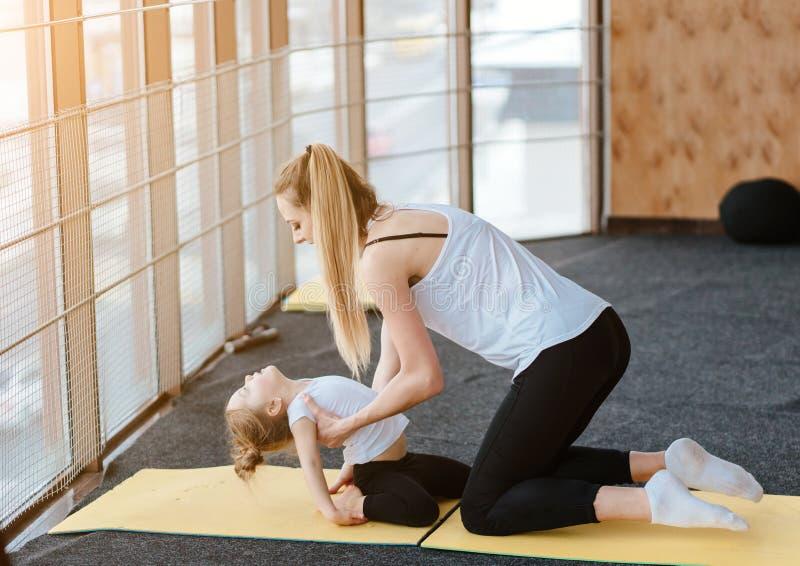 La mamá y la hija juntos realizan diversos ejercicios foto de archivo