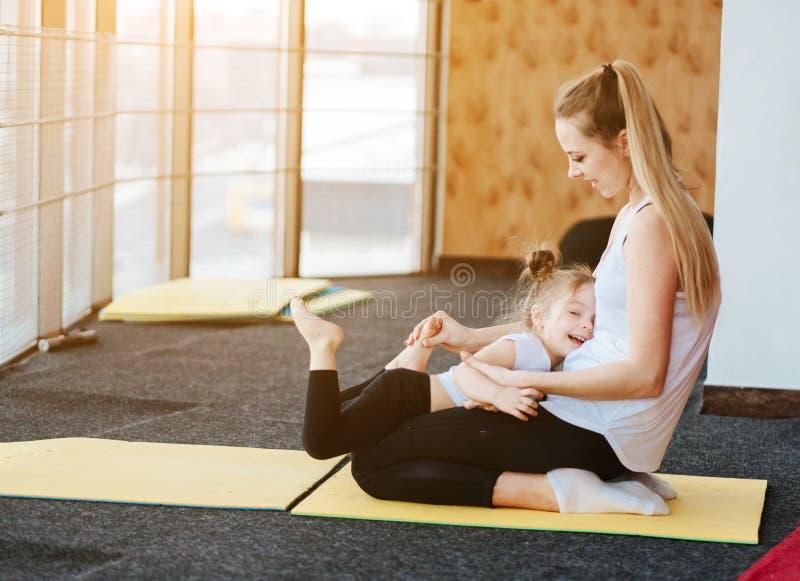 La mamá y la hija juntos realizan diversos ejercicios imágenes de archivo libres de regalías