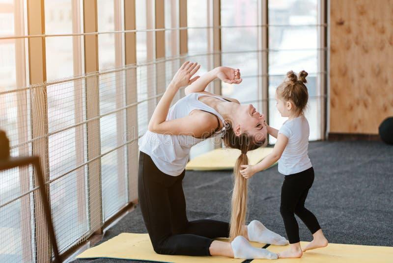 La mamá y la hija juntos realizan diversos ejercicios fotos de archivo libres de regalías