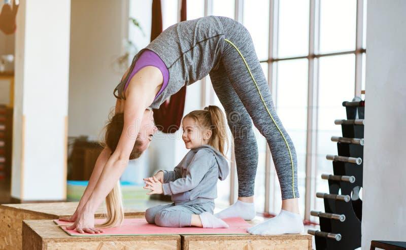 La mamá y la hija juntos realizan diversos ejercicios fotos de archivo