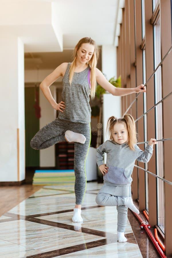 La mamá y la hija juntos realizan diversos ejercicios fotografía de archivo libre de regalías