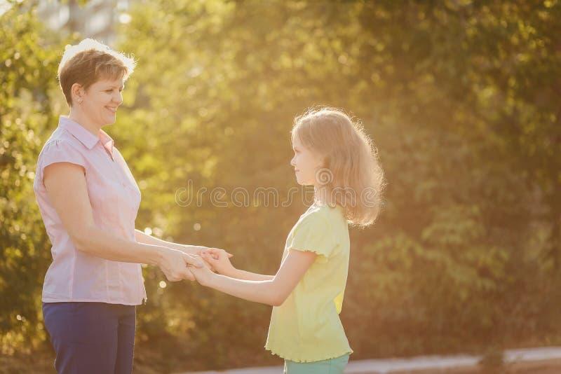 La mamá y la hija miran uno a y llevan a cabo las manos imagen de archivo