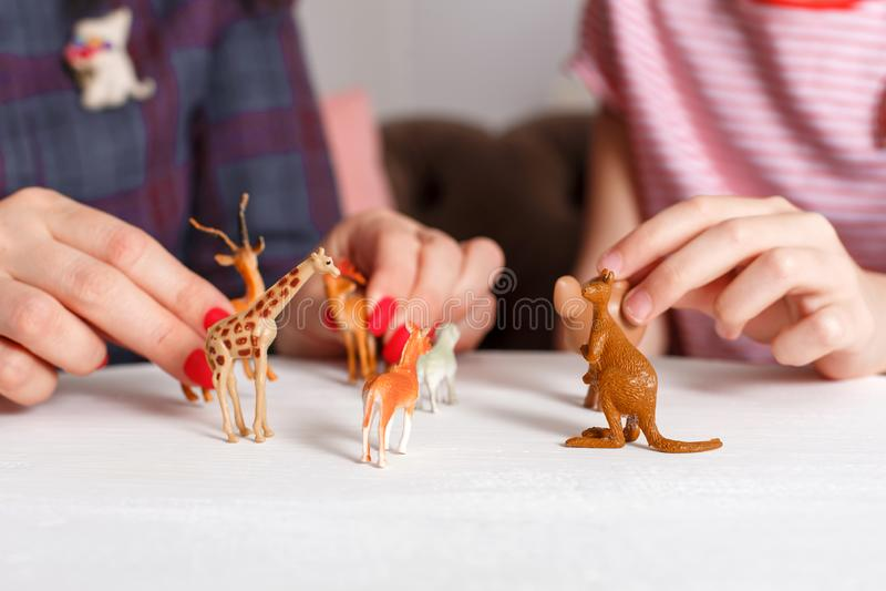 La mamá y la hija pasan el tiempo junto, se sientan en el sofá, charlando y jugando con los animales del juguete Madres e hijas d imagen de archivo libre de regalías