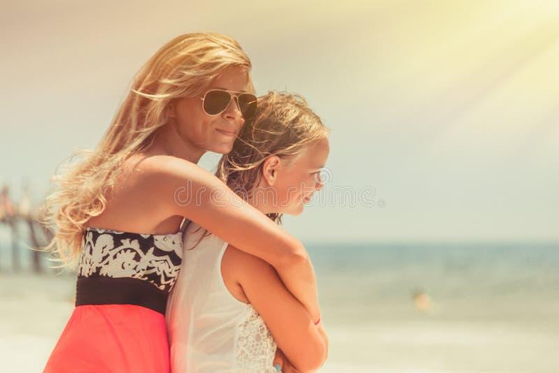 La mamá y la hija permanecen de abrazo en el mar y miran el agua con sueños fotos de archivo libres de regalías