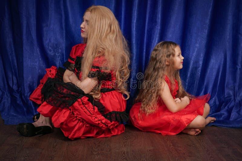 La mamá y la hija son ofendidas y que se sientan en el piso la mamá está intentando establecer paz y amistad con el niño fotografía de archivo