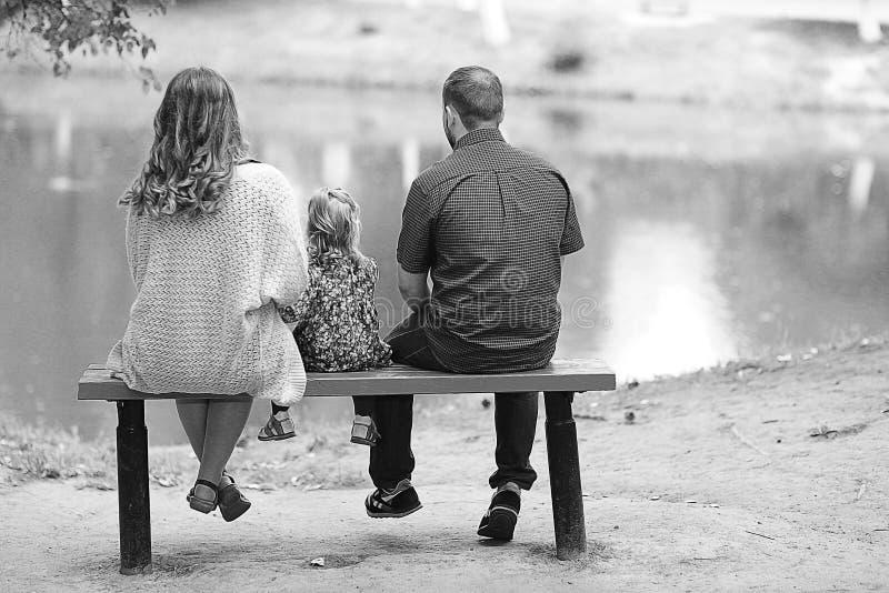 La mamá y la hija joven y el papá que caminan en verano parquean foto de archivo