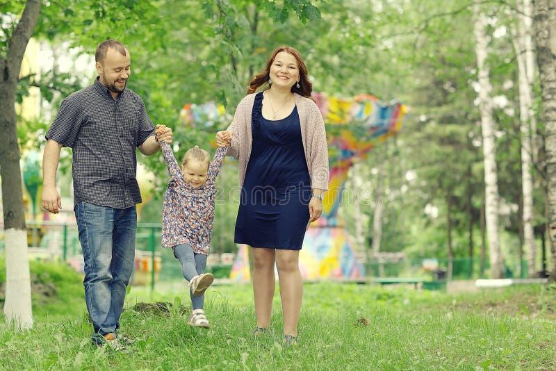 La mamá y la hija joven y el papá que caminan en verano parquean foto de archivo libre de regalías