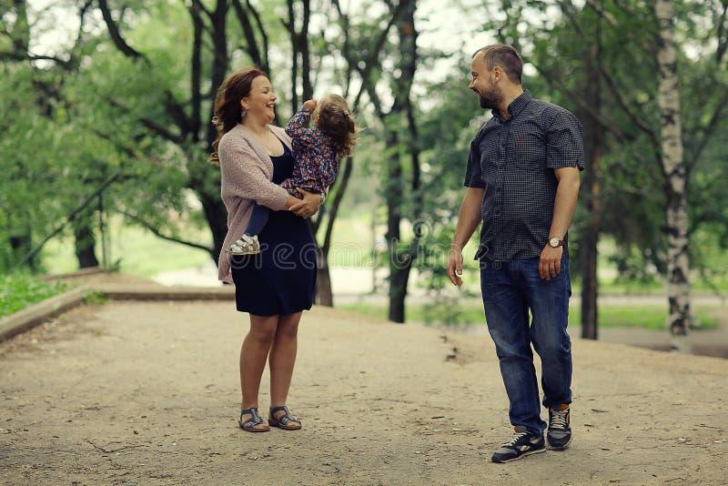 La mamá y la hija joven y el papá que caminan en verano parquean fotos de archivo