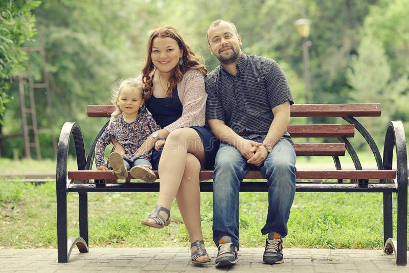 La mamá y la hija joven y el papá que caminan en verano parquean fotos de archivo libres de regalías
