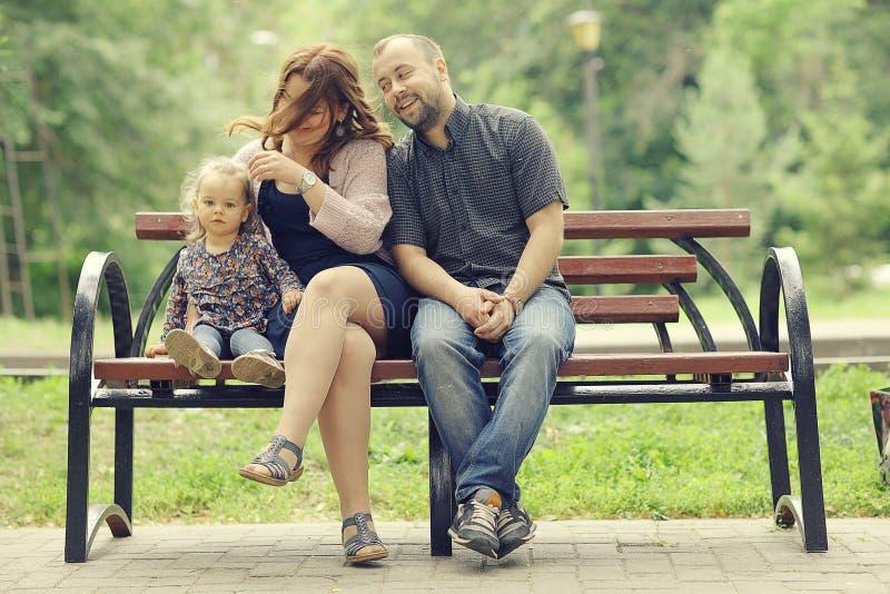 La mamá y la hija joven y el papá que caminan en verano parquean imágenes de archivo libres de regalías