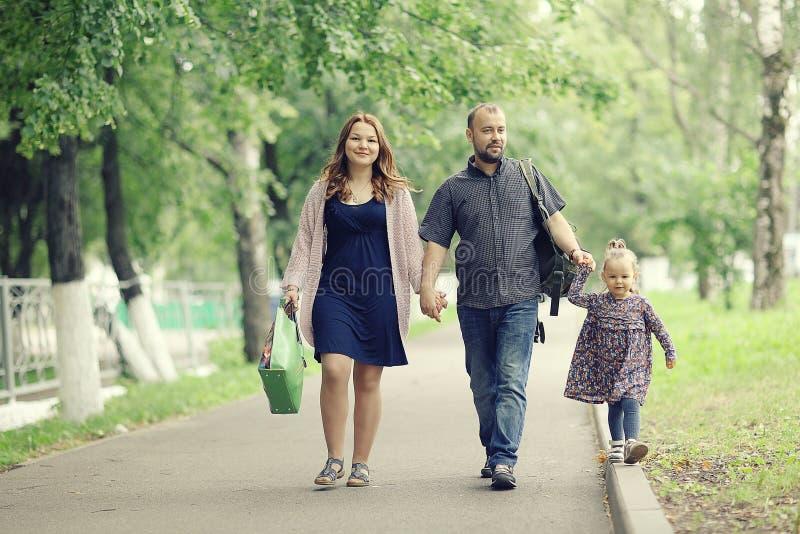 La mamá y la hija joven y el papá que caminan en verano parquean fotografía de archivo