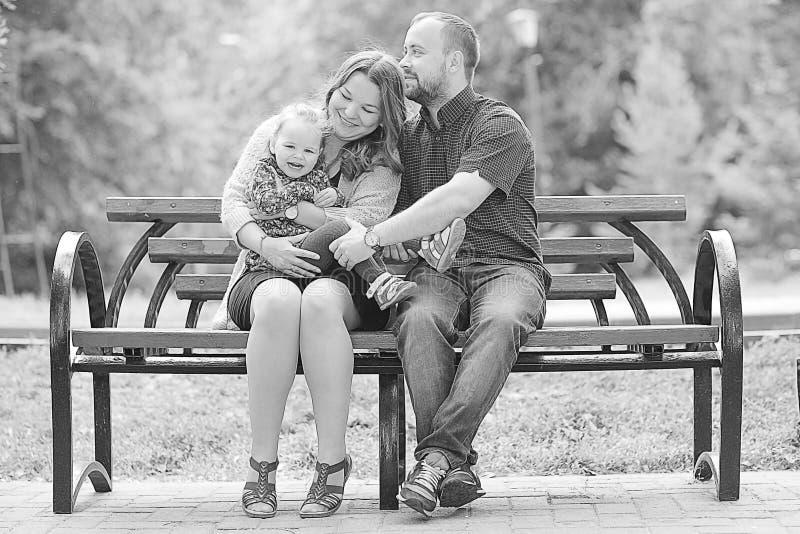 La mamá y la hija joven y el papá que caminan en verano parquean imagenes de archivo