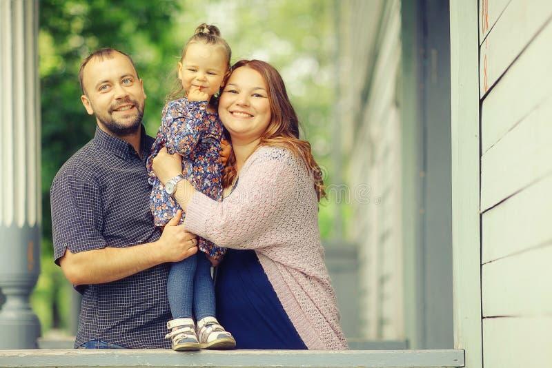 La mamá y la hija joven y el papá que caminan en verano parquean imagen de archivo