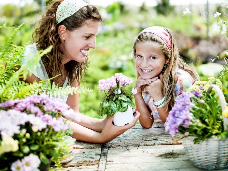 La mamá y la hija se divierten en el trabajo de cultivar un huerto fotos de archivo