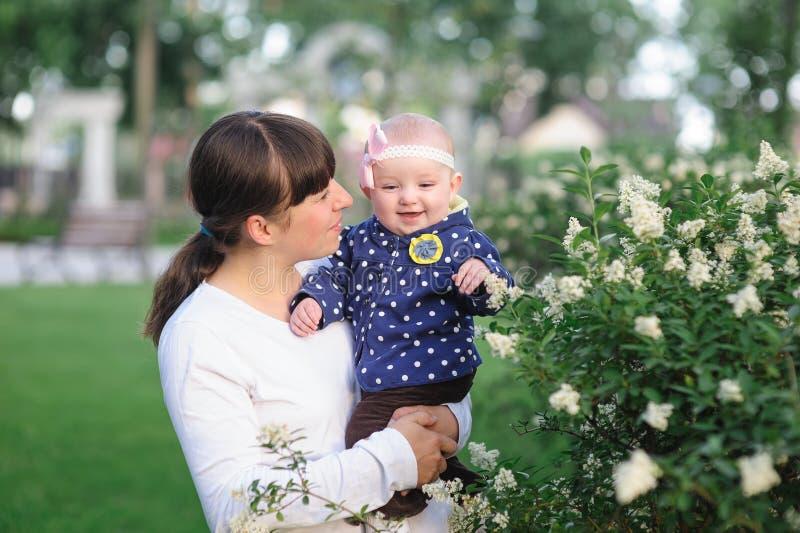 La mamá y la pequeña hija del bebé que caminan en la primavera parquean fotos de archivo libres de regalías
