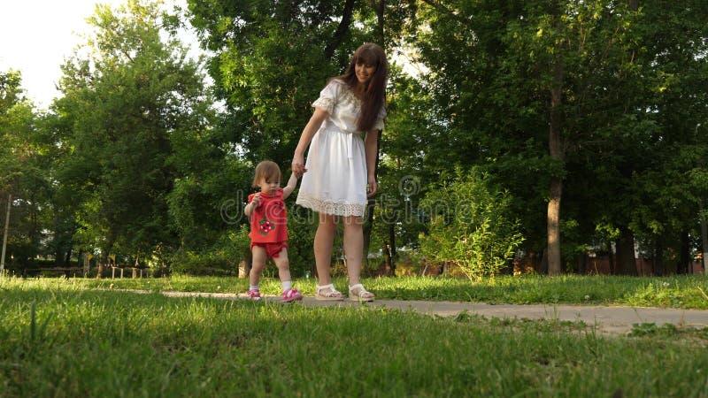 La mamá y poca hija están caminando a lo largo de la trayectoria en el parque del verano los primeros pasos del bebé con la mamá imagen de archivo libre de regalías
