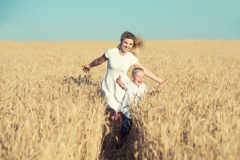 La mamá y poco hijo están corriendo alrededor del campo de trigo fotografía de archivo libre de regalías