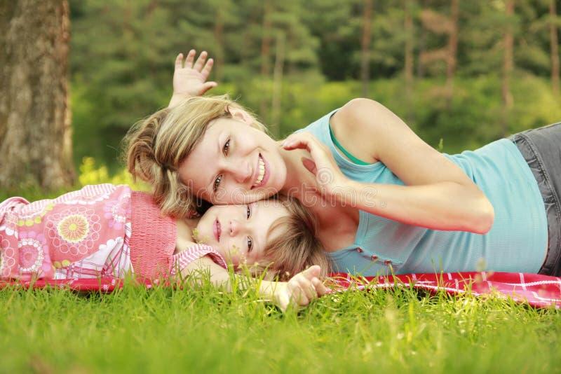 La mamá y su pequeña hija mienten en la hierba fotos de archivo libres de regalías