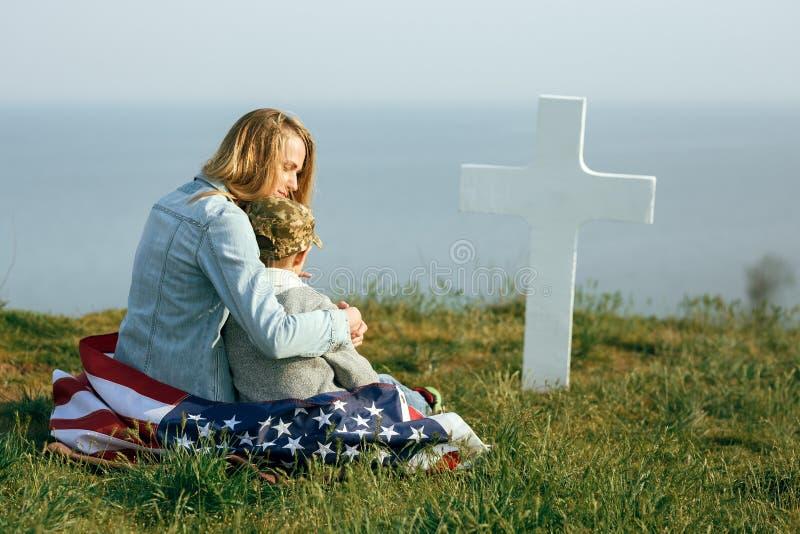 La mam? y el hijo se est?n sentando en el sepulcro de un soldado La mam? trajo a su hijo al sepulcro de su padre el Memorial Day  fotos de archivo libres de regalías