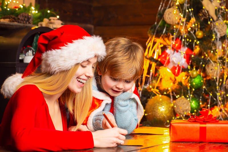 La mam? y el ni?o juegan juntos Nochebuena Familia feliz D?a de fiesta de la familia El venir de Santa Claus Muchacho de la madre foto de archivo libre de regalías