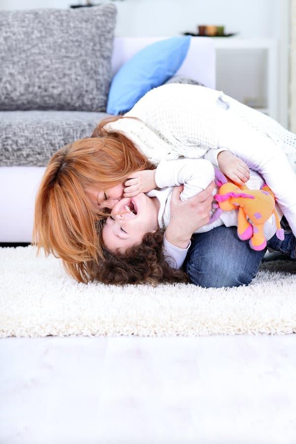 La mama cosquillea a su niño imagen de archivo libre de regalías