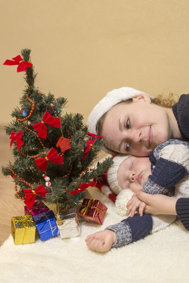 La maman étreint son bébé de sommeil dans le chapeau d'une Santa image stock
