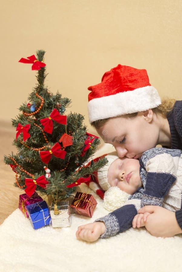 La maman étreint son bébé de sommeil dans le chapeau d'une Santa image libre de droits