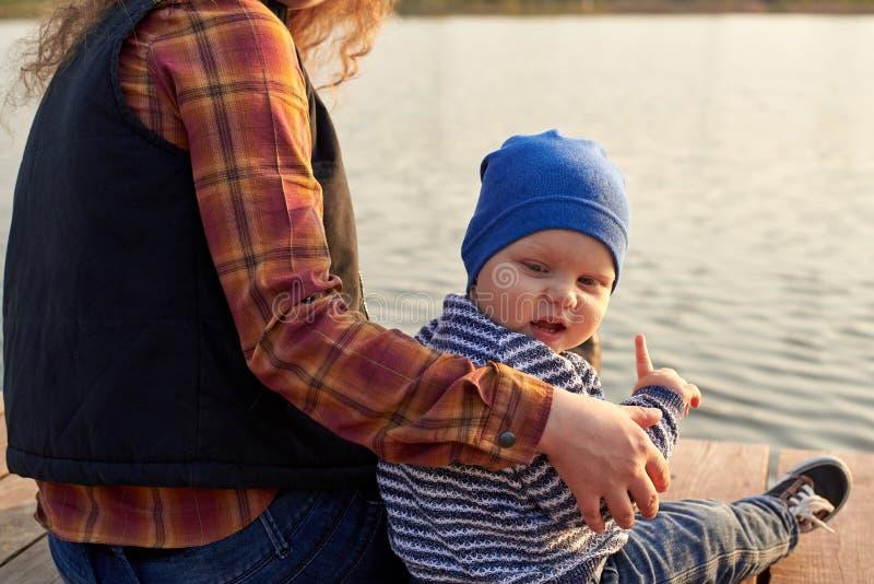 La maman étreint son fils sur le pilier sur la rivière image stock