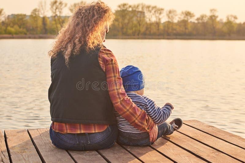 La maman étreint son fils sur le pilier sur la rivière, photo modifiée la tonalité photo libre de droits