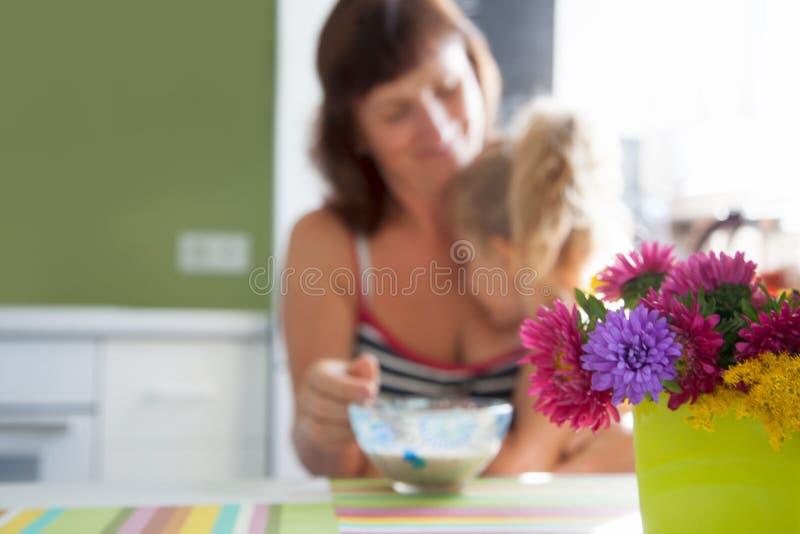 La maman alimente au petit déjeuner de fille le dérivé avec sa mère en Th images libres de droits