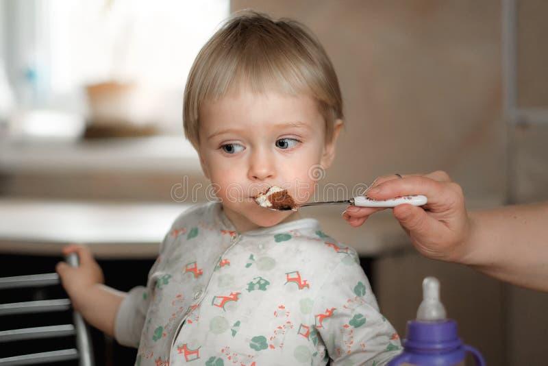 La maman alimente le bébé d'une cuillère photos libres de droits