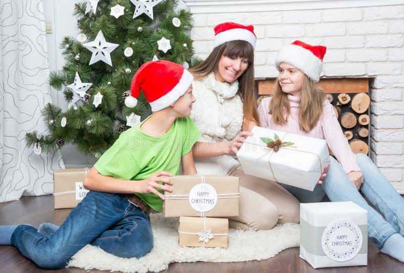 La maman avec des enfants considère des cadeaux image libre de droits