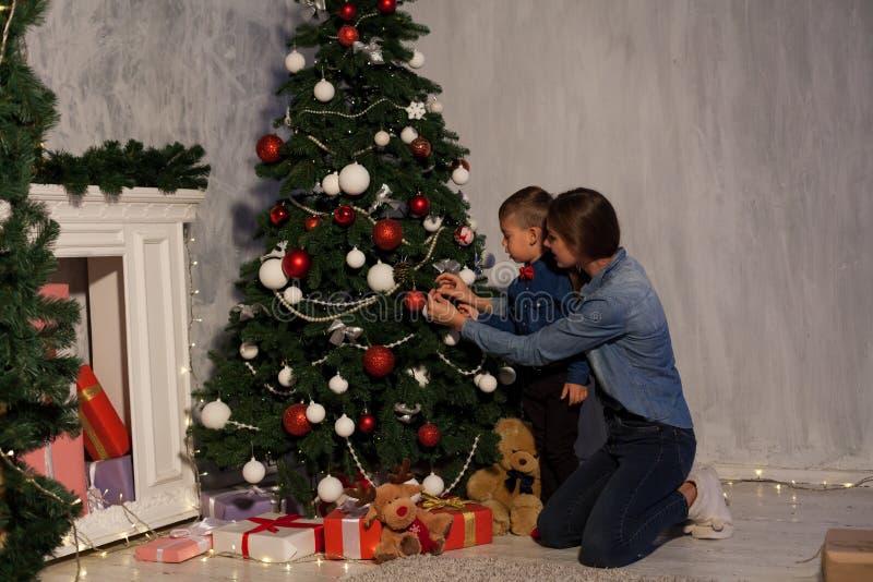 La maman avec le fils orner l'arbre de Noël allume la nouvelle année de Noël images stock