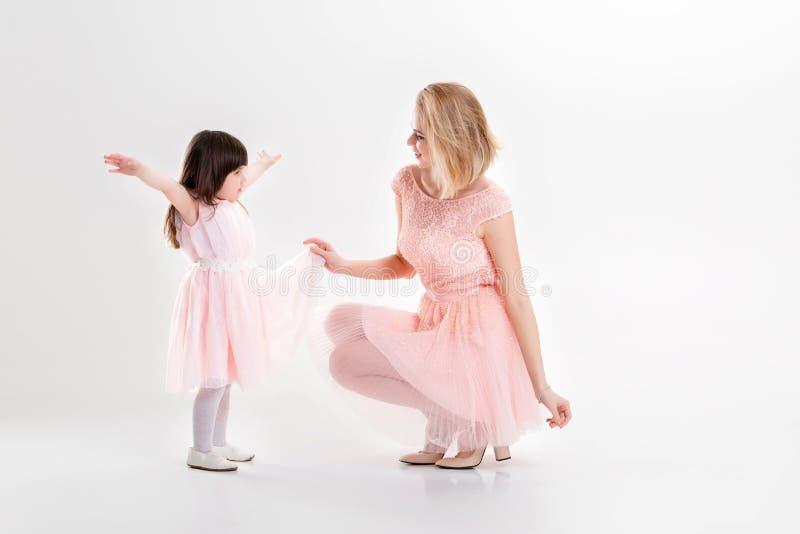La maman blonde et la petite fille douce dans le rose habille des princesses image stock